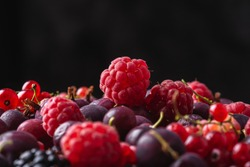 Tasty fresh ripe raspberry, blackberry, gooseberry and red currant berries, healthy food texture on black background, angle view macro