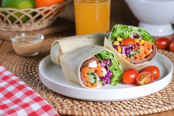 Tasty fresh salad wraps or tortilla wraps with kebab beef meat and fresh vegetables, served in white plate on wooden table.