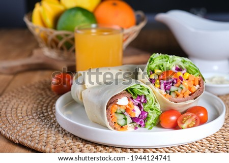 Tasty fresh salad wraps or tortilla wraps with kebab beef meat and fresh vegetables, served in white plate on wooden table. Photo stock ©