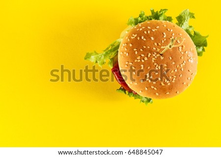 Tasty fresh unhealthy hamburgers with ketchup and vegetables on yellow vibrant bright background. Top View with Copy Space.
