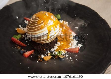 Tasty fruit ice-cream dessert with berries decorated with nitrogen steam