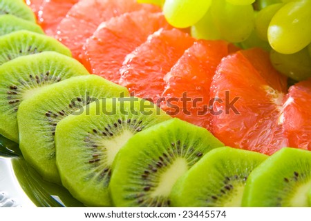 Tasty fruit salad on tray. Multiple fruits.
