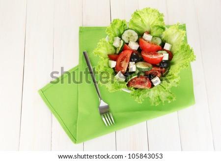 tasty Greek salad on white wooden background - stock photo
