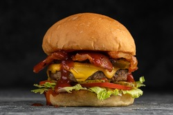 Tasty grilled beef burger with fried bacon and eggs, cheese, tomatoes and lettuce.