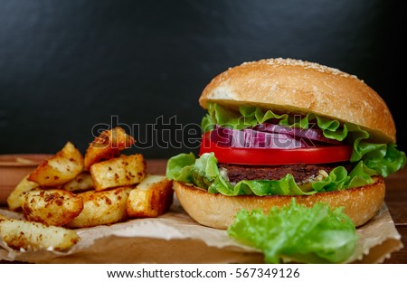 Tasty grilled beef burger with lettuce and potatoes on paper and dark wooden background. Big hamburger for lunch. Fast food photo.