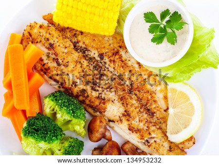 Tasty grilled fish fillet with fresh vegetables and sauce on white plate, luxury dinner in restaurant, delicious barbecue meat, healthy nutrition