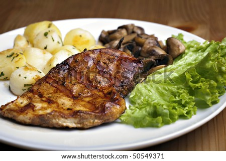 Tasty grilled food, chicken meat, roasted potatoes and mushrooms and sallet
