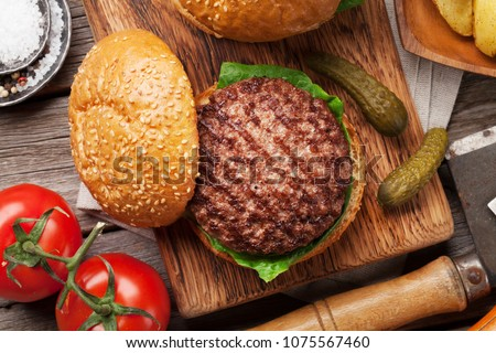 Tasty grilled home made burger cooking with beef, tomato, cheese, cucumber and lettuce. Top view #1075567460