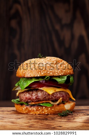 Tasty grilled home made burger with beef, tomato, cheese, cucumber and lettuce. With copy space