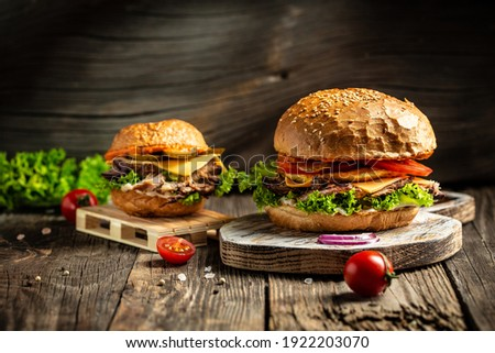Tasty grilled homemade burgers with beef, tomato, cheese, bacon and lettuce on rustic wooden background. fast food and junk food concept.