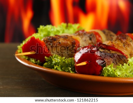 tasty grilled meat and vegetables on plate, on fire background - stock photo