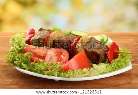 tasty grilled meat and vegetables on skewer on plate, on wooden table