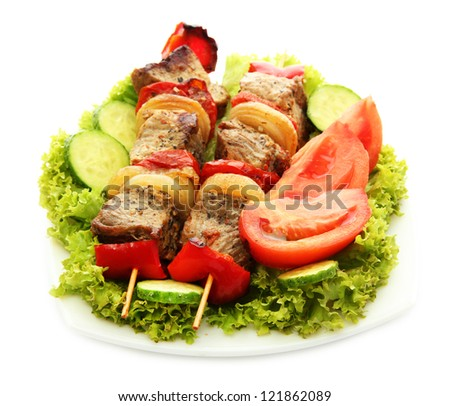 tasty grilled meat and vegetables on skewers on plate, isolated on white