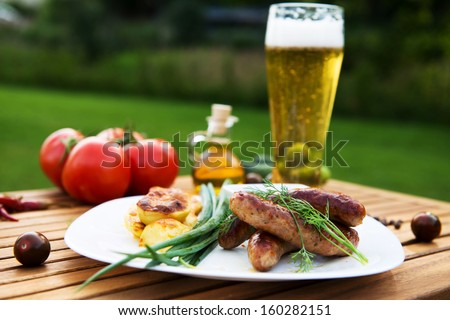 tasty grilled meat sausages  on dish and vegetable