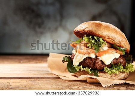 Tasty grilled prawn and beef burger with lettuce and mayonnaise served on pieces of brown paper on a rustic wooden table of counter, with copyspace