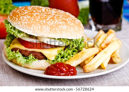 Tasty hamburger with fries and soda in the background.