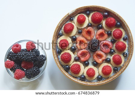 tasty healthy and useful breakfast oatmeal porridge with lot of berries blueberry, raspberry, blackberry, cherry, banana in round ceramic bowl and small bowl of berries. from the top view. above shot #674836879