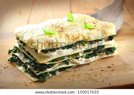 Tasty healthy portion of vegetarian spinach lasagne with alternating layers of pasta and fresh green spinach leaves with cheese on a wooden board