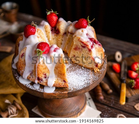 tasty homemade bundt cake with strawberries and white glaze on top on wooden cake stand on rustic table Foto stock ©