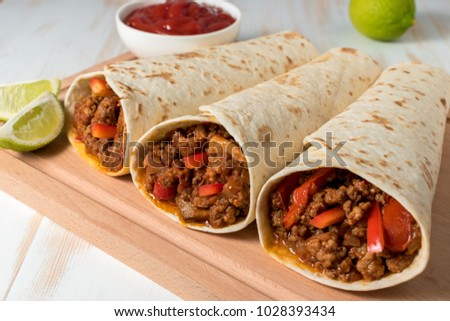 Tasty homemade burrito with vegetables and beef on wooden background.