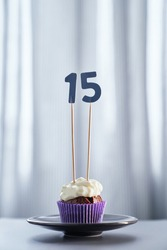 Tasty homemade chocolate birthday or anniversary cupcake with creamy topping and number 15 fifteen on black plate and bright background. Minimalistic invitation card concept. High quality image