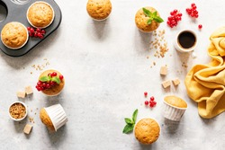 Tasty homemade muffins with red berries and brown sugar and cup of coffee espresso on bright grey concrete background, copy space. Sweet food frame