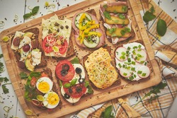 Tasty, homemade small sandwiches with various ingredients served on wooden chopping board. Vege kitchen concept.