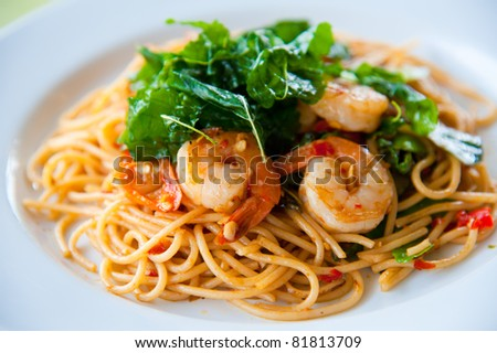 tasty hot and spicy spaghetti with cream, cheese and parsley close up