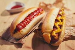 Tasty hot dogs on paper on wooden background