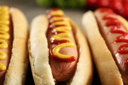Tasty hot-dogs with vegetables on wooden background, close up