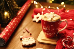Tasty hot drink in cup with inscription Believe in Magic, space for text. Christmas atmosphere