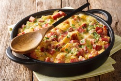 Tasty hot homemade strata with ham, onions, cheese and eggs close-up in a pan on the table. horizontal