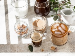Tasty ice coffee with milk, cream and set with different types of coffee drinkson gray background with copy space. Ice coffee with milk, espresso, cappuccino and mocha coffee. Cold summer drink.