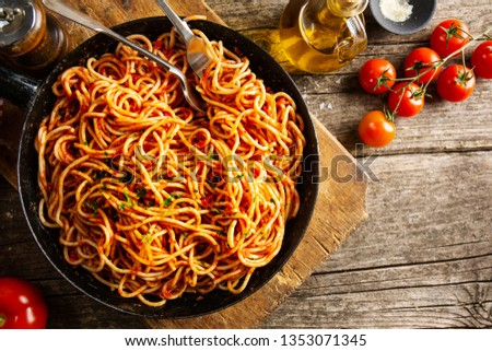 Tasty italian classic spaghetti with tomato sauce cooked in pan. Old wooden table background. Rustical. View from above. Cooking process #1353071345