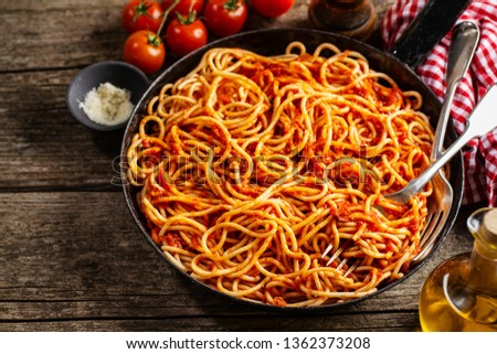 Tasty italian classic spaghetti with tomato sauce cooked in pan. Old wooden table background. Rustical. View from above. Cooking process
