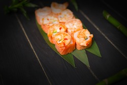 Tasty Japanese seafood sushi roll with salmon tataki and roasted black tiger shrimps on top served on bamboo leaves with bamboo plant and sticks on black wooden background
