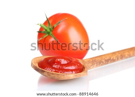 Tasty ketchup in wooden spoon and tomato isolated on white