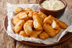 Tasty Kibbeling is a Dutch dish prepared with pieces of cod served with sauce closeup in the plate on the table. Horizontal