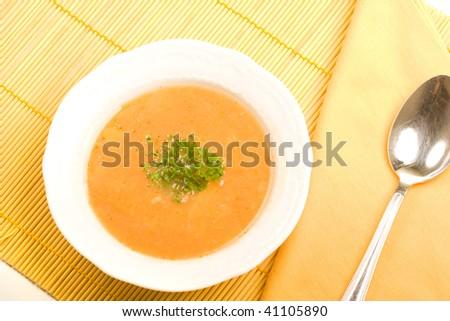 Tasty kohlrabi soup on orange table cover.