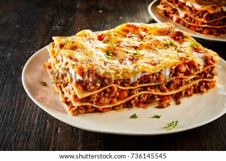 Tasty lasagne with meat covered with cheese served on white plate #736145545