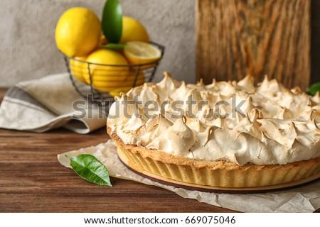 Tasty lemon meringue pie on wooden table, closeup