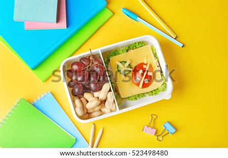 Tasty lunch with sandwich in box and stationery on yellow background
