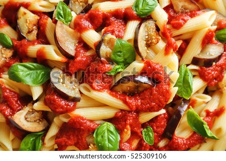 Tasty macaroni with ketchup, eggplant slices and basil, close up view
