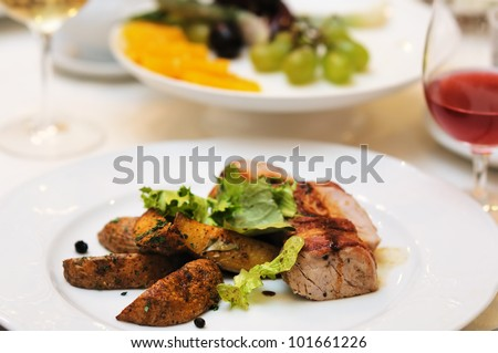 Tasty meat and baked potato on white plate