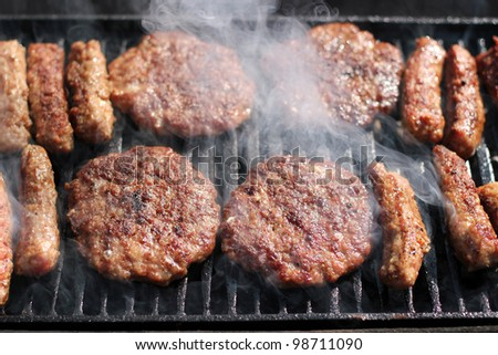 Tasty meat roasted on a grill. Delicious Hamburgers and kebabs on the grill. Barbecue party. Delicious meat on bbq grill. Summer barbecue with mixed meat.