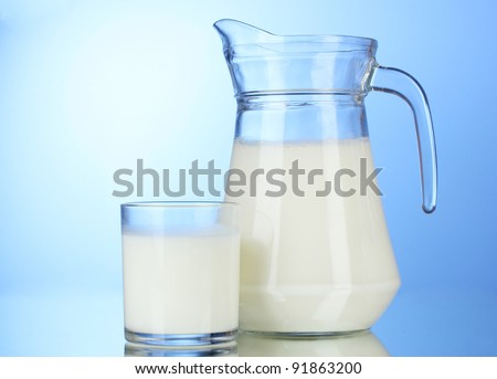 Tasty milk in jug and glass on blue background