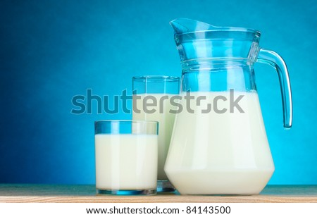 Tasty milk in jug and glasses on blue background