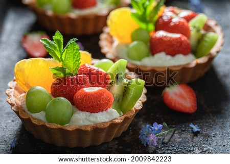 Tasty mini tart with various fruits. Sweet summer dessert. Tart with cream and fruit.
