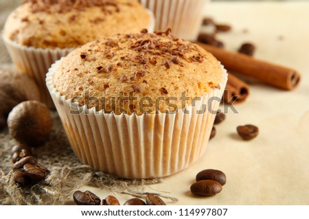 tasty muffin cakes with chocolate, spices and coffee seeds, on beige background - stock photo