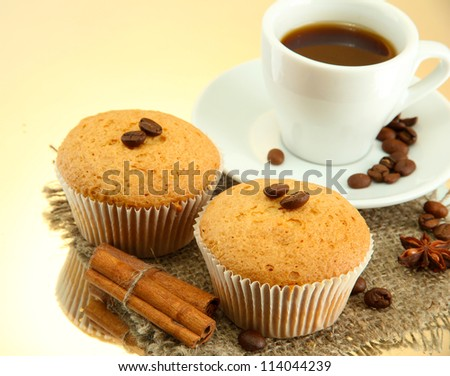 tasty muffin cakes with spices on burlap and cup of coffee, on beige background
